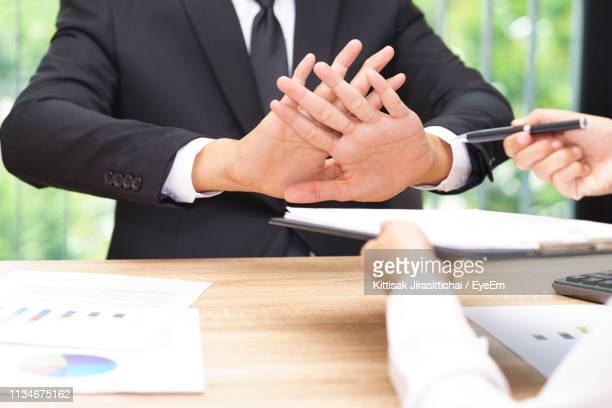 cropped hands of person giving documents and pen to sign while man refusing over table - weigeren stockfoto's en -beelden