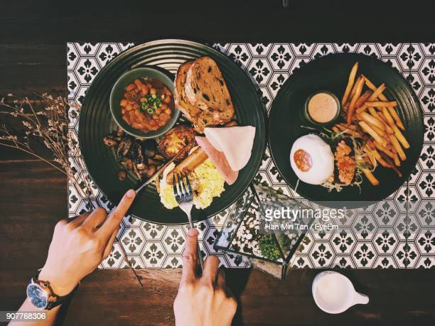 Cropped Hands Of Person Having Food On Table