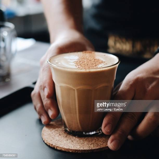 Cropped Hands Of Person Holding Coffee At Cafe