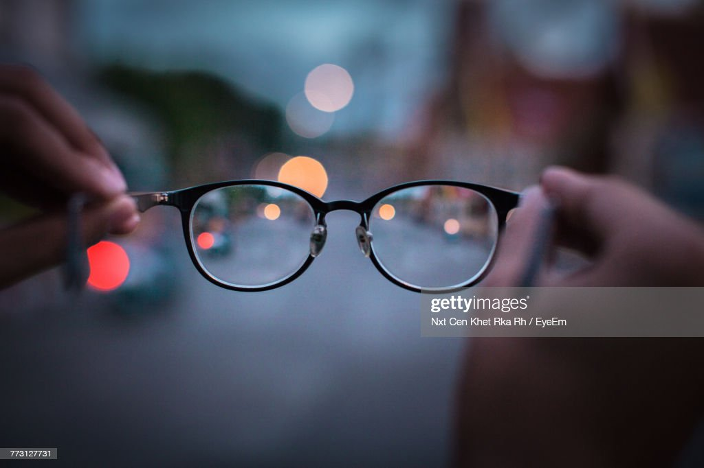 Cropped Hands Of Person Holding Eyeglasses During Sunset : Stock-Foto