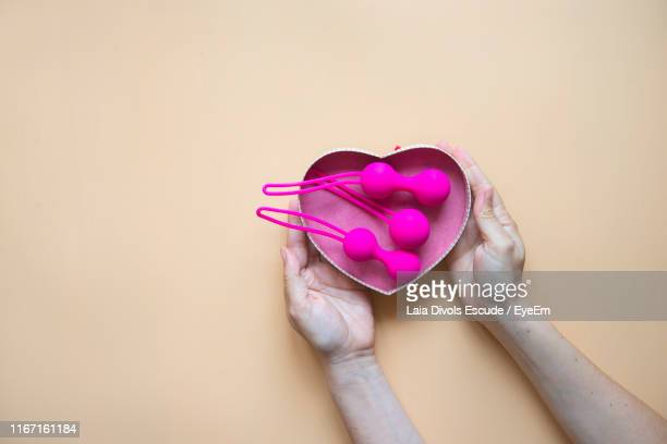 cropped hands of person holding heart shape container with sex toys against beige background - sex toy stock photos and pictures