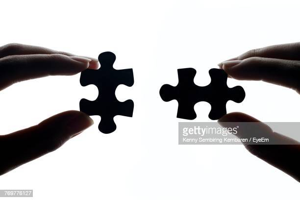 cropped hands of person holding jigsaw piece against white background - jigsaw piece stock pictures, royalty-free photos & images