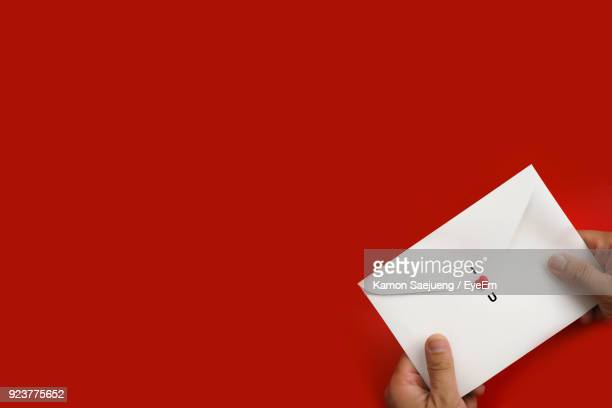 cropped hands of person holding love letter on table - love letter stock photos and pictures
