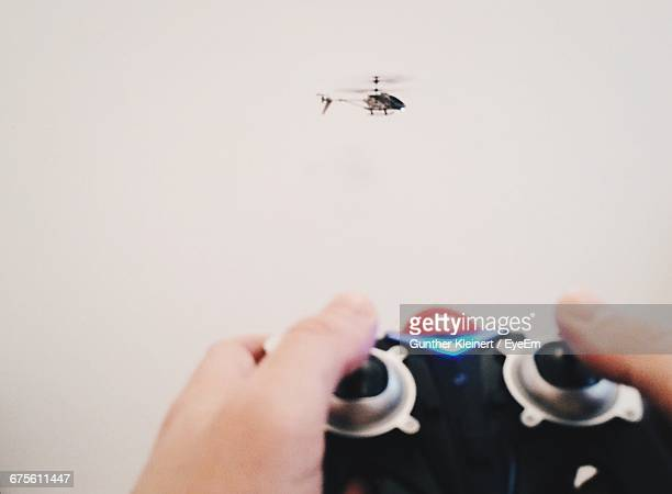 cropped hands of person holding remote control against toy helicopter - remote control helicopter stock photos and pictures