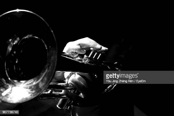 cropped hands of person holding trumpet in darkroom - tromba foto e immagini stock