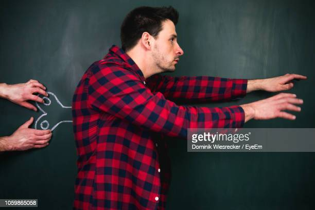 Cropped Hands Of Person Making Man Wind-Up Toy By Blackboard