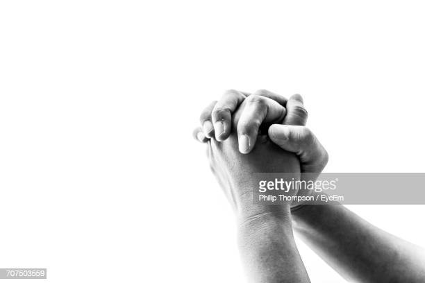Cropped Hands Of Person Praying Against White Background