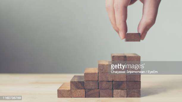 cropped hands of person stacking wooden blocks on table - building block stock pictures, royalty-free photos & images