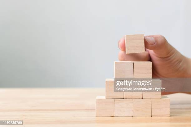 cropped hands of person stacking wooden blocks on table - toy block stock pictures, royalty-free photos & images