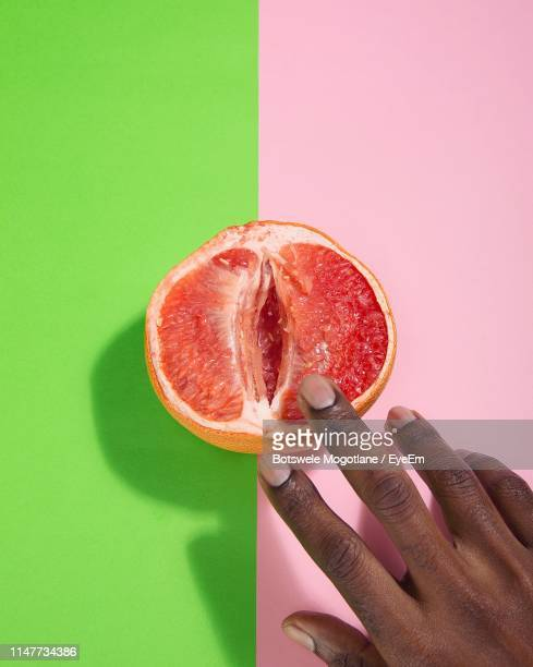 cropped hands of person touching grapefruit over two tone background - grapefruit red stock pictures, royalty-free photos & images