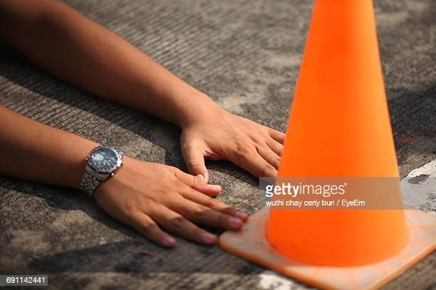 Cropped Hands Of Person Touching On Traffic Cone On Street