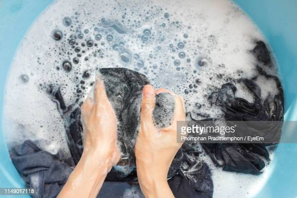 cropped hands of person washing laundry in bucket - waschen stock-fotos und bilder