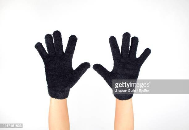 cropped hands of person wearing mittens against white background - mitten stock pictures, royalty-free photos & images