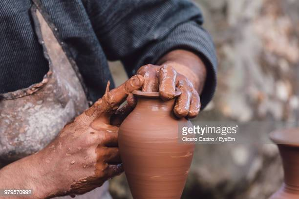 cropped hands of potter making clay pot at pottery - potter stock pictures, royalty-free photos & images