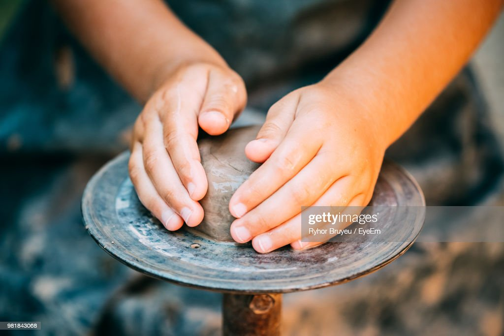 Cropped Hands Of Potter Making Clay Pot At Pottery : Stock Photo
