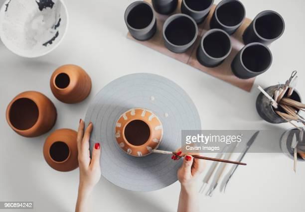 cropped hands of potter painting ceramics on table in workshop - tonkeramik stock-fotos und bilder