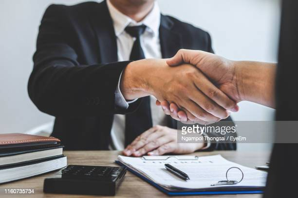 cropped hands of real estate agent giving handshake to customer in office - abmachung stock-fotos und bilder