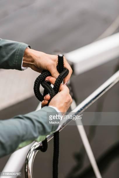 cropped hands of senior female instructor tying rope on yacht's railing - binden stock-fotos und bilder