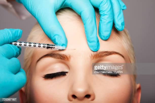 cropped hands of surgeon giving botox injection to woman against gray background - botox stock pictures, royalty-free photos & images