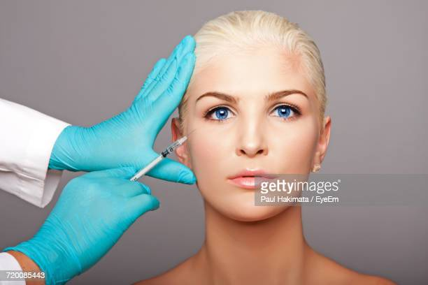 Cropped Hands Of Surgeon Giving Botox Injection To Woman Against Gray Background