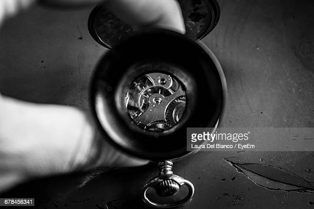 Cropped Hands Of Watch Maker Holding Magnifying Glass Against Gears