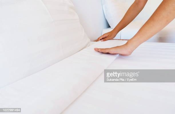 cropped hands of woman adjusting sheet on bed - sheet stock pictures, royalty-free photos & images