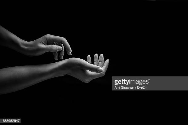 cropped hands of woman against black background - black and white hands stock pictures, royalty-free photos & images