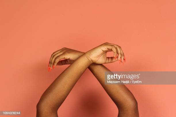 cropped hands of woman against colored background - menselijke ledematen stockfoto's en -beelden