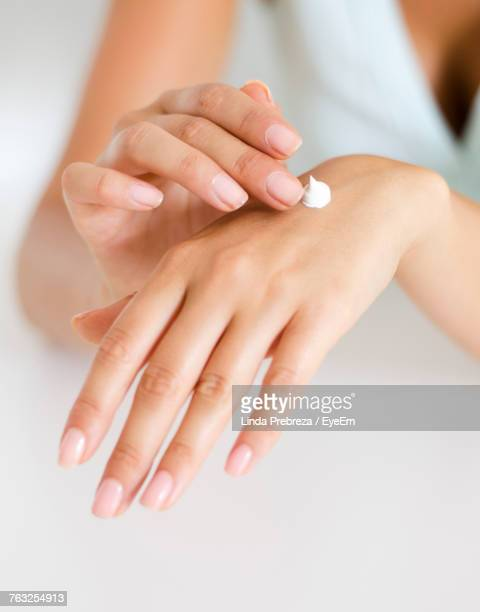 Cropped Hands Of Woman Applying Cream