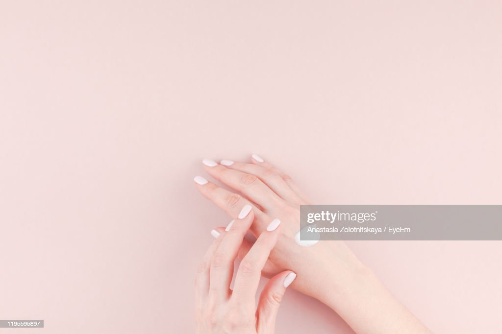 Cropped Hands Of Woman Applying Moisturizer Pink Background : Stockfoto