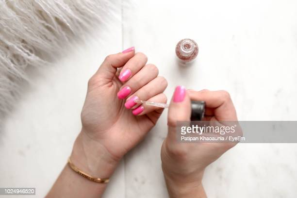 cropped hands of woman applying pink nail polish on table - nail varnish stock pictures, royalty-free photos & images