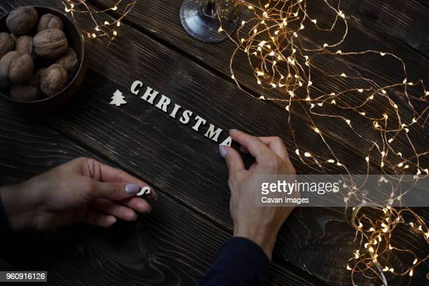 Cropped hands of woman arranging Christmas letters on wooden table