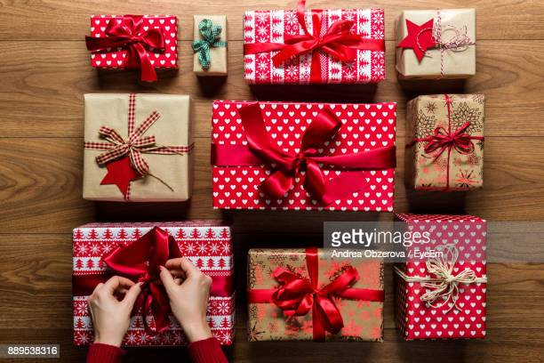 Cropped Hands Of Woman Arranging Christmas Presents On Hardwood Floor