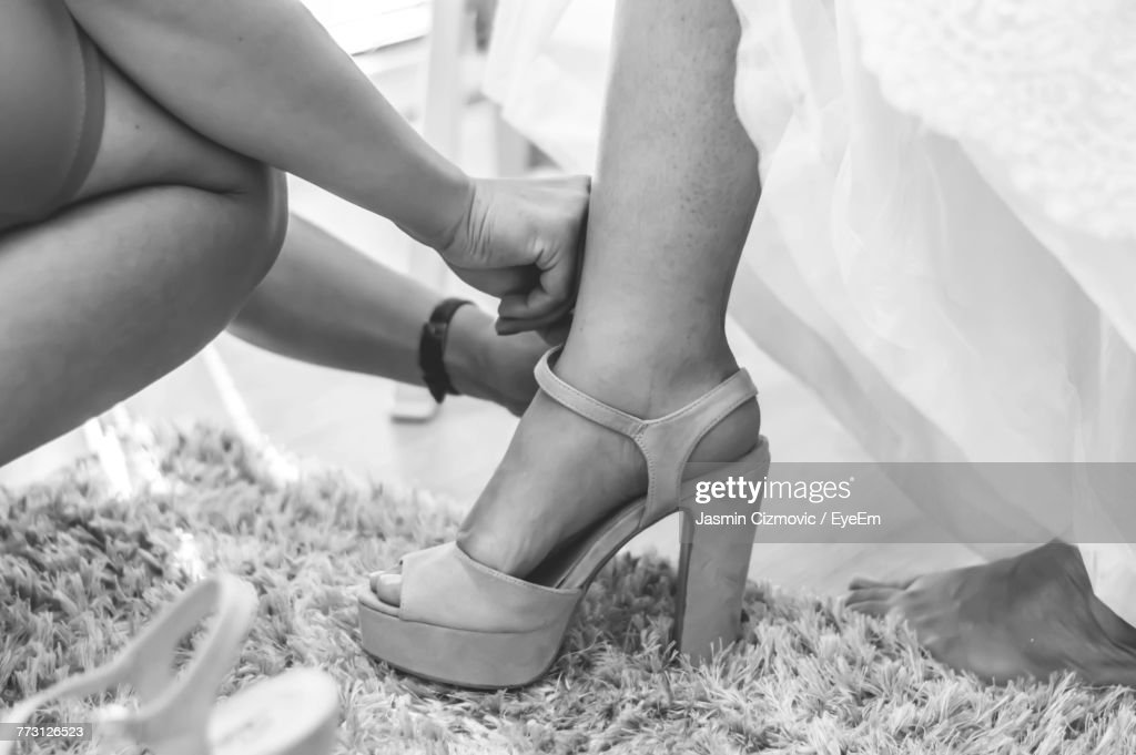 Cropped Hands Of Woman Assisting Bride In Wearing Sandal : Photo
