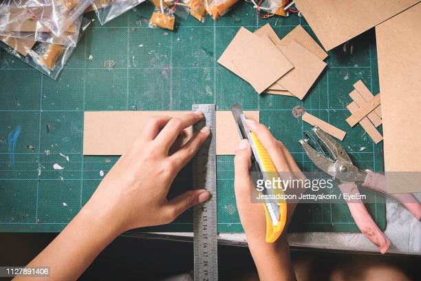 cropped hands of woman cutting cardboard using ruler and utility knife on table - utility knife stock pictures, royalty-free photos & images