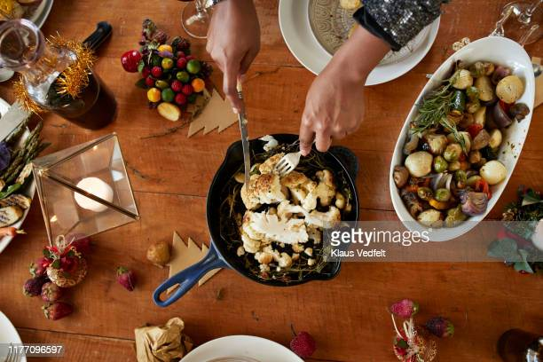 cropped hands of woman cutting cauliflower in pan - holiday stock pictures, royalty-free photos & images