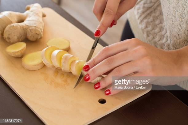 cropped hands of woman cutting ginger on board in kitchen at home - ginger stock photos and pictures