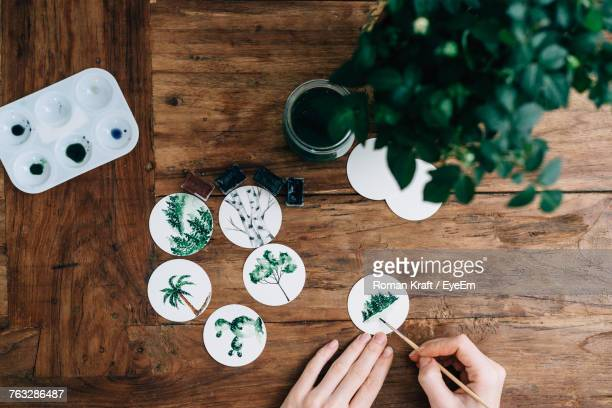 cropped hands of woman doing aquarelle at wooden table - hobbies stock pictures, royalty-free photos & images