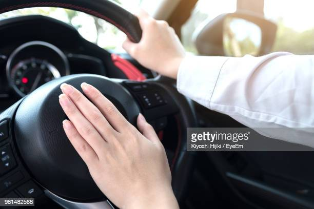 Cropped Hands Of Woman Driving Car