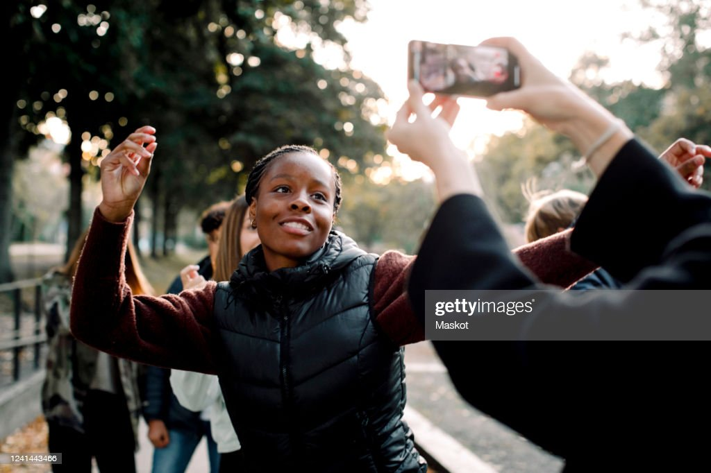 Cropped hands of woman filming teenage girl dancing on street in city : Stock Photo