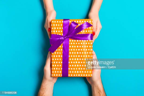 cropped hands of woman giving gift to male friend against blue background - giving stock pictures, royalty-free photos & images