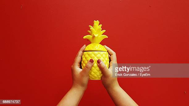 cropped hands of woman holding artificial pineapple against red background - erick pulgar fotografías e imágenes de stock