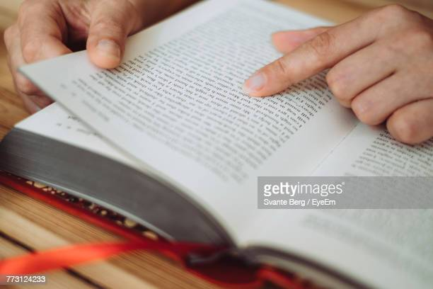 Cropped Hands Of Woman Holding Book At Table