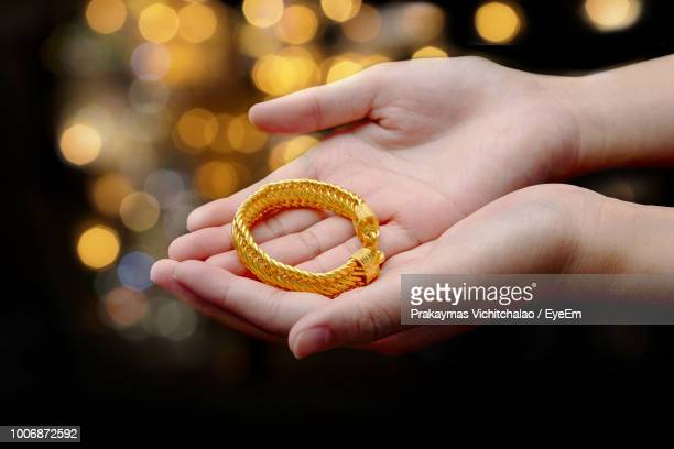 cropped hands of woman holding bracelet against illuminated lights - bracelet stock pictures, royalty-free photos & images