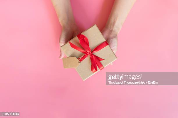 cropped hands of woman holding christmas present over pink background - gift stock pictures, royalty-free photos & images