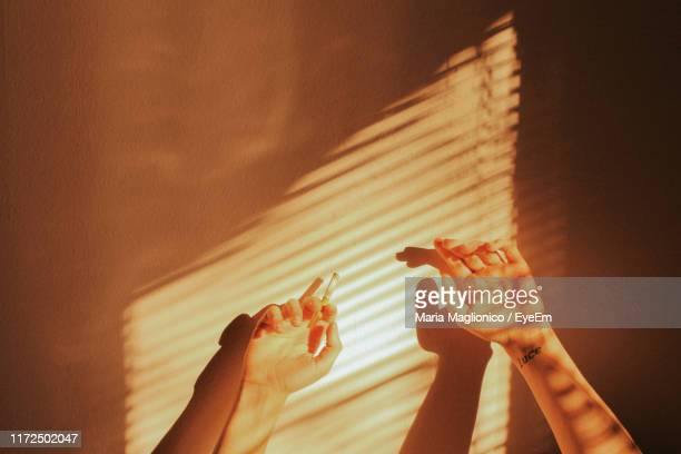 cropped hands of woman holding cigarette against wall at home - 25 29歳 ストックフォトと画像