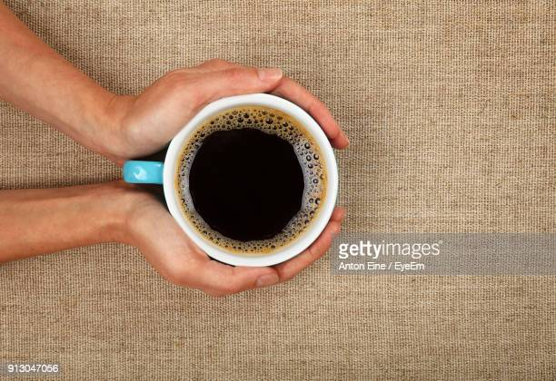 Cropped Hands Of Woman Holding Coffee Cup