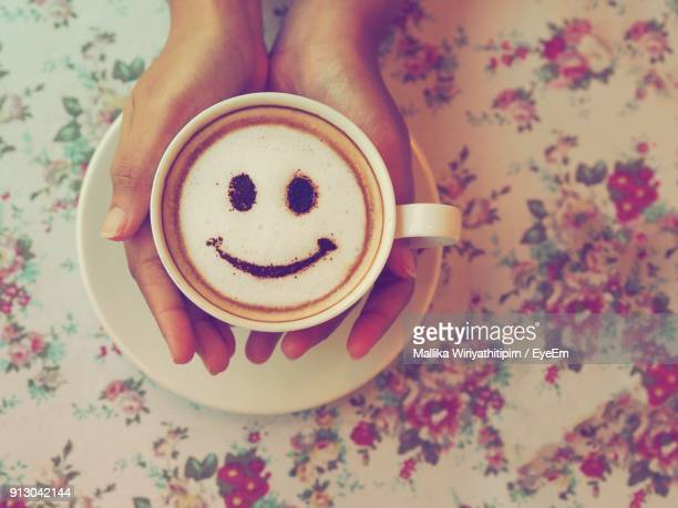cropped hands of woman holding coffee on table - smiley face stock pictures, royalty-free photos & images