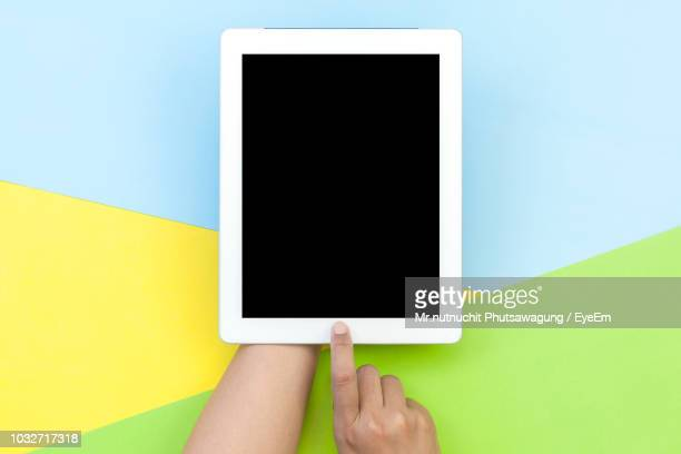 cropped hands of woman holding digital tablet over colored background - ツートンカラー ストックフォトと画像