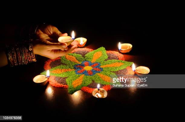 cropped hands of woman holding diya over rangoli at night - rangoli stock pictures, royalty-free photos & images
